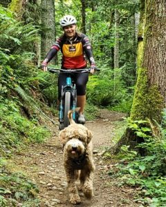 Julie Duggan riding bike with dog